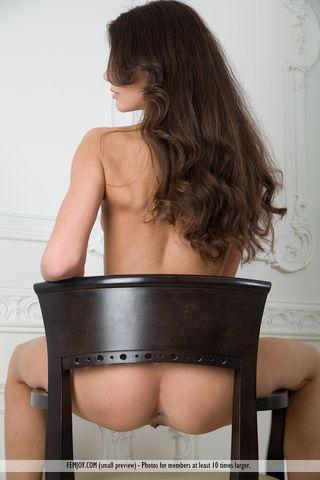 Брюнетка позирует без трусиков на черном деревянном стуле и стонет