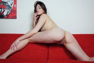 Модель на красном диване натирает рукой мягкую писечку и острые соски