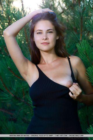 Брюнетка в лесу под соснами показывает на камеру приятеля теплое влагалище