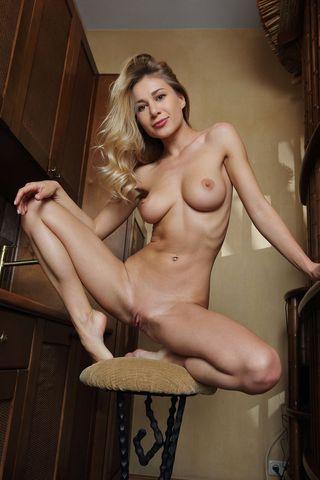 Девка на стуле на кухне раздвигает ноги на камеру и фоткает глубокое влагалище