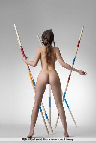 Спортсменка около копий для легкой атлетики позирует в стиле ню