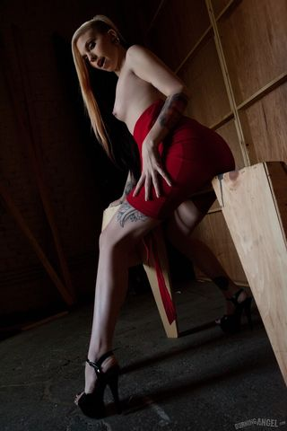 Татуированная блонди задирает красное платье и гладит пальцами бритую вагину