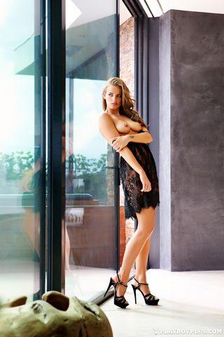 Загорелая модель с тату на лобке снимает черное полупрозрачное платье
