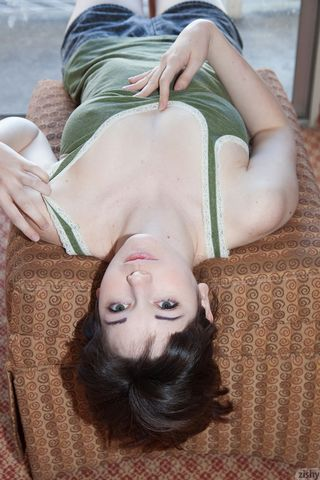 Скромница мнет руками сисечки через ткань зеленой майки и возбуждает соски