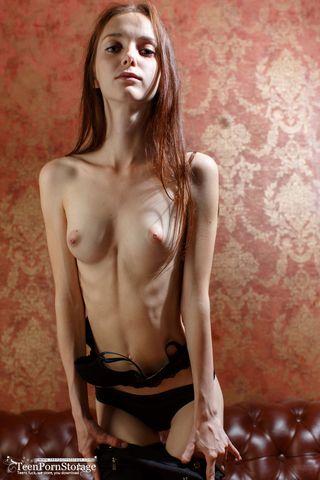 Модель на коричневом кожаном диване делает фотографии в стиле ню